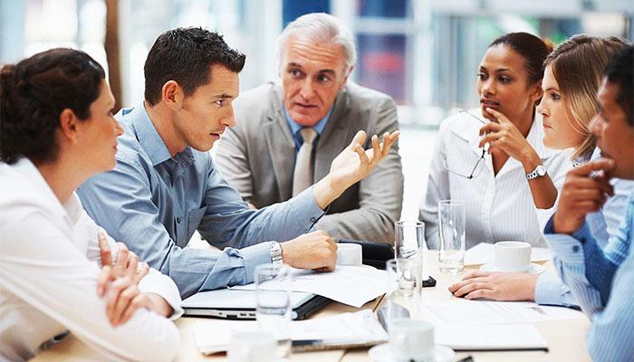 会議で発言する若いビジネスマン